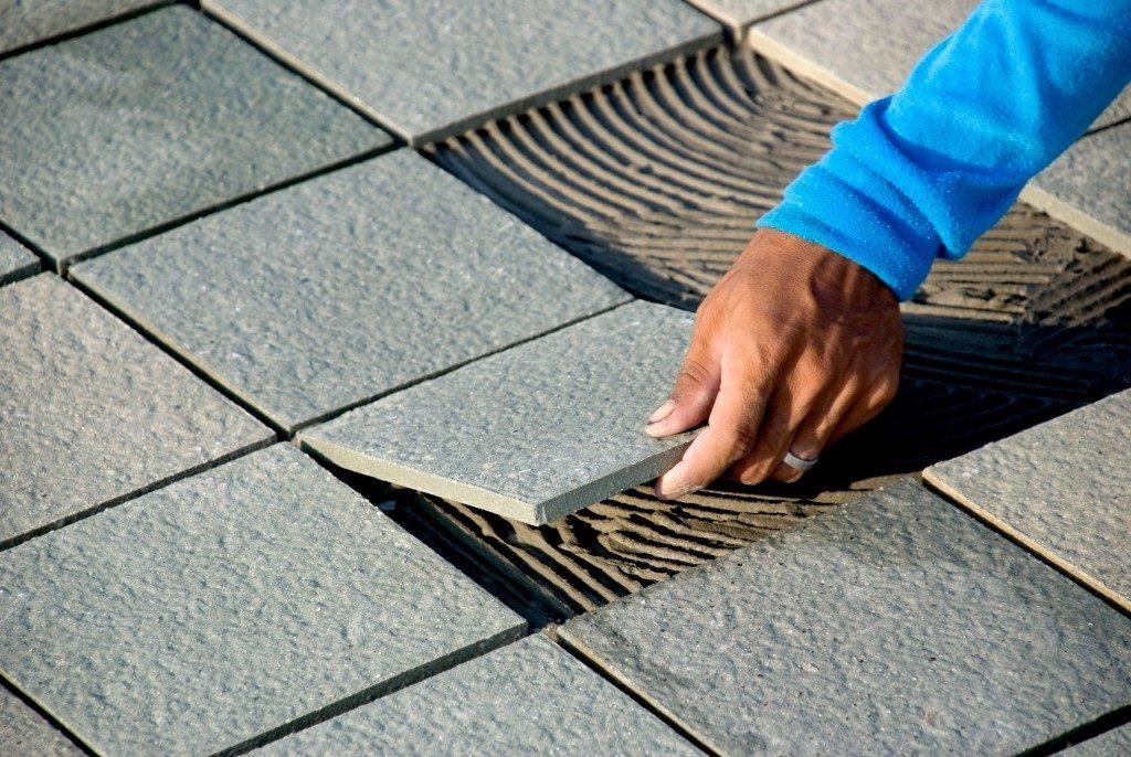 Man installing concrete tiles
