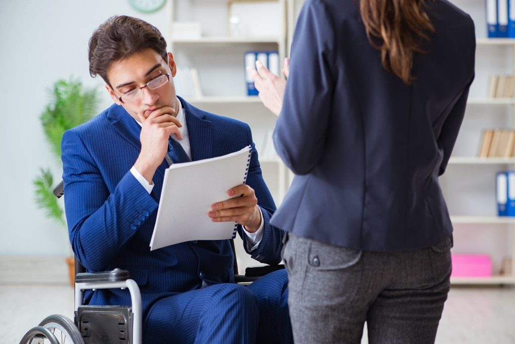 Person with disability with lawyer discussing about documents