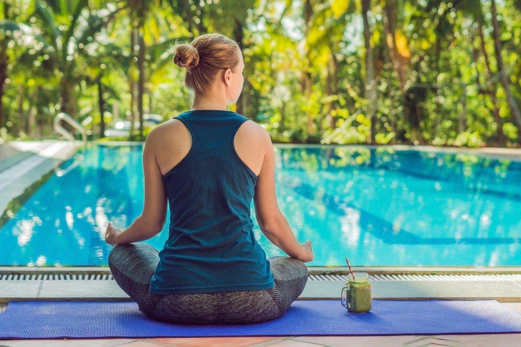 woman meditating near the pool