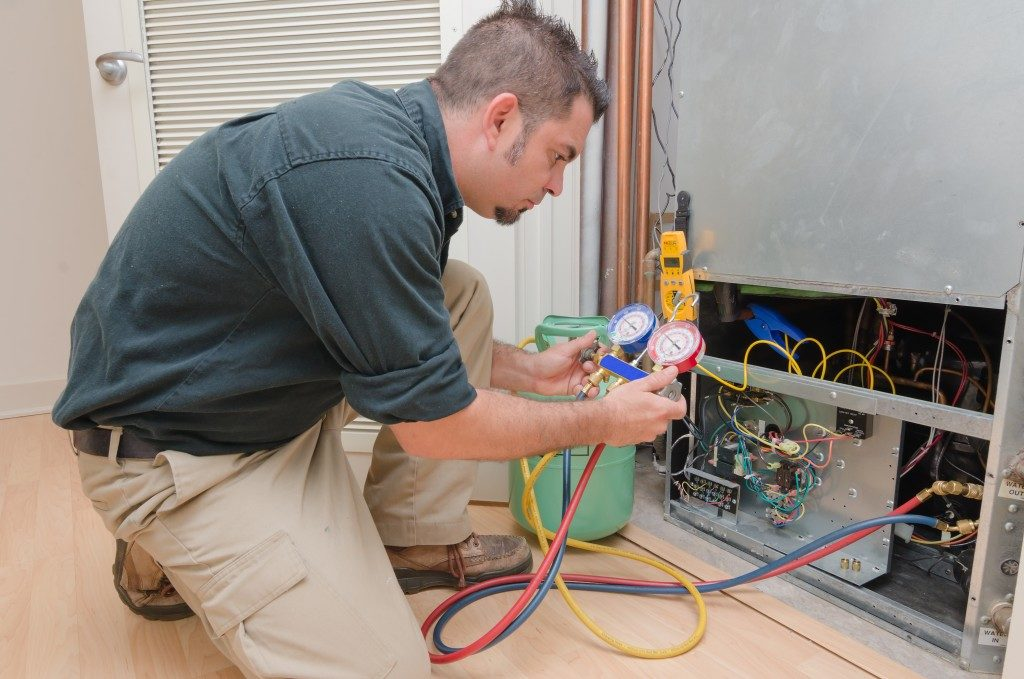 man checking temperature of heating system