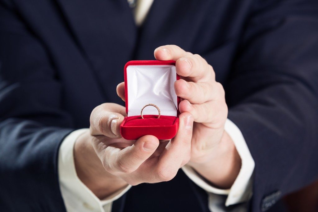 Close up of man holding wedding ring and gift box