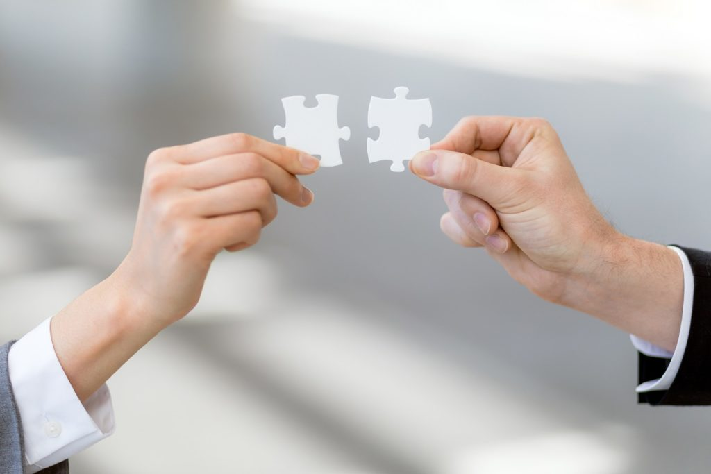 people connecting puzzle pieces