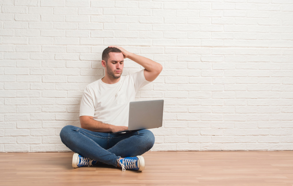 man holding a laptop, stressed out