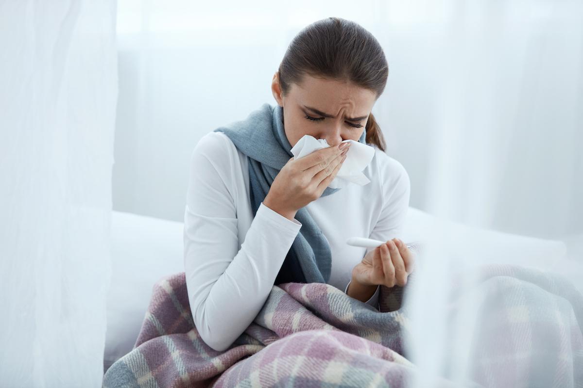 woman sneezing onto a tissue