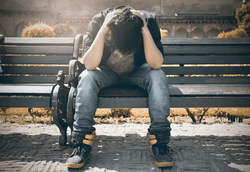 Depressed man sitting on a bench
