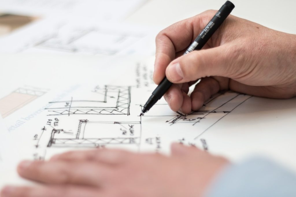 person drawing blueprints