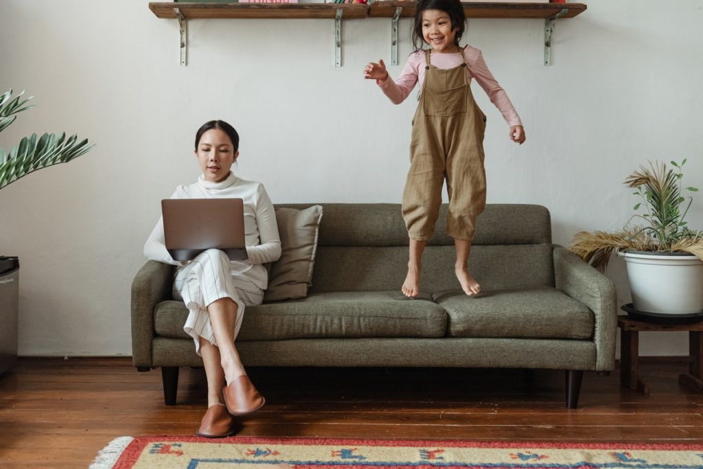 woman working from home with daughter jumping on the sofa