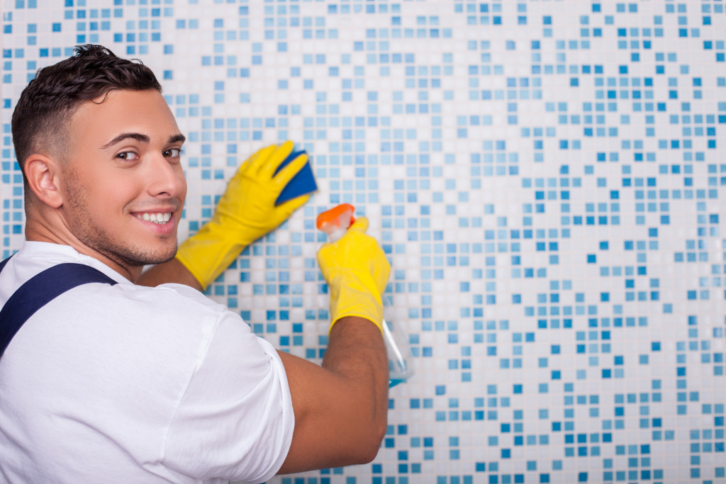 man cleaning bathroom wall